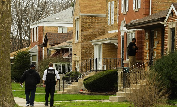 Chicago Police walk through the 9400 block of South Forest, where Cook County associate judge Raymond Myles was fatally wounded on Monday. - LESLIE ADKINS/FOR THE SUN-TIMES