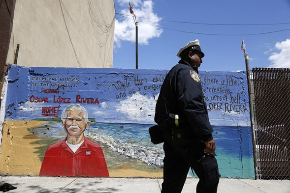 A police officer walks past a mural of Oscar López Rivera in New York. - AP PHOTO/SETH WENIG