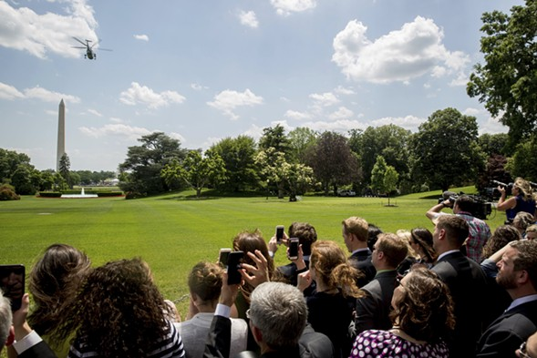 Members of the media and White House staff watched as Marine One departed from the South Lawn of the White House Friday. - AP PHOTO/ANDREW HARNIK