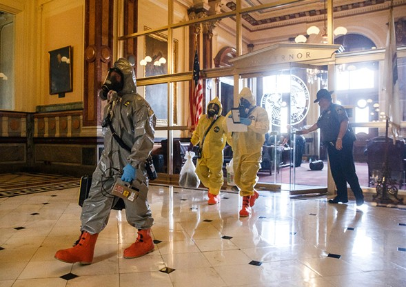 The Springfield fire department and hazmat unit exit after inspecting the governor's office, where a woman allegedly threw a powdery substance during the overtime session at the Illinois State Capitol Thursday. - JUSTIN L. FOWLER/THE STATE JOURNAL-REGISTER VIA AP