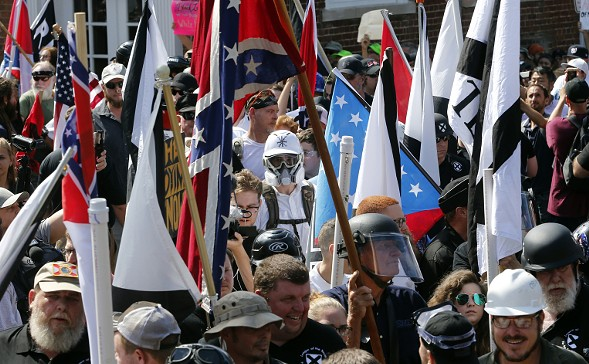 White nationalist demonstrators walk into the entrance of Lee Park surrounded by counter demonstrators Saturday in Charlottesville, Virginia. - AP PHOTO/STEVE HELBER
