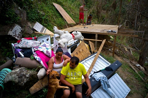 Yadira Sortre and William Fontan Quintero pose next to what is left of their belongings, destroyed by Hurricane Maria, in the San Lazaro neighborhood of Moravis, Puerto Rico. - AP PHOTO/RAMON ESPINOSA