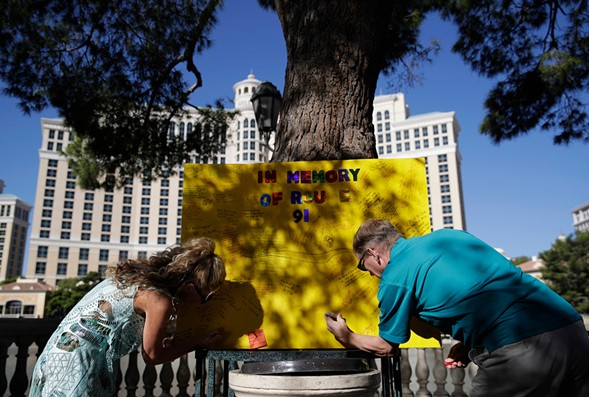 People leave messages at a makeshift memorial for victims of the mass shooting in Las Vegas. - AP PHOTO/JOHN LOCHER