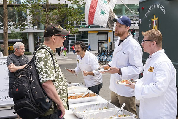 Army vet Aaron Hughes and navy vet Michael Applegate help Rakowitz serve food during an Enemy Kitchen activation. - NATHAN KEAY/MCA CHICAGO