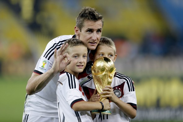 Germany's Miroslav Klose poses with the World Cup trophy and his sons in 2014 - AP PHOTO/NATACHA PISARENKO,FILE