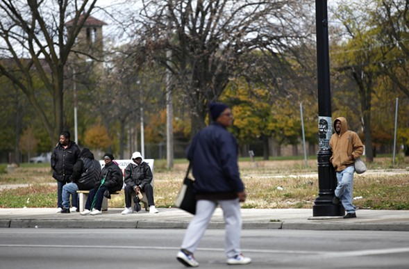 Residents of the Englewood neighborhood of Chicago wait for a bus. - AP PHOTO/CHARLES REX ARBOGAST