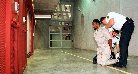 A 1998 photo of Gregory Bradford, incarcerated at Tamms, having leg shackles put on before a visit to the law library. Bradford is now serving time at Menard, one of Illinois's three maximum security prisons. - AP PHOTO/CEASAR MARAGNI