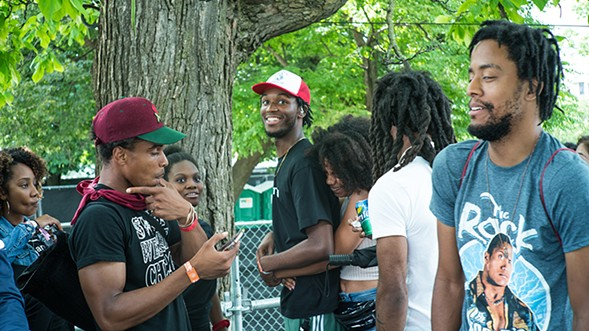 Saba hangs with friends and family before his set. He's in the red and white hat, Frsh Waters has on a maroon hat, and Joseph Chilliams wears a Rock T-shirt. - TIM NAGLE