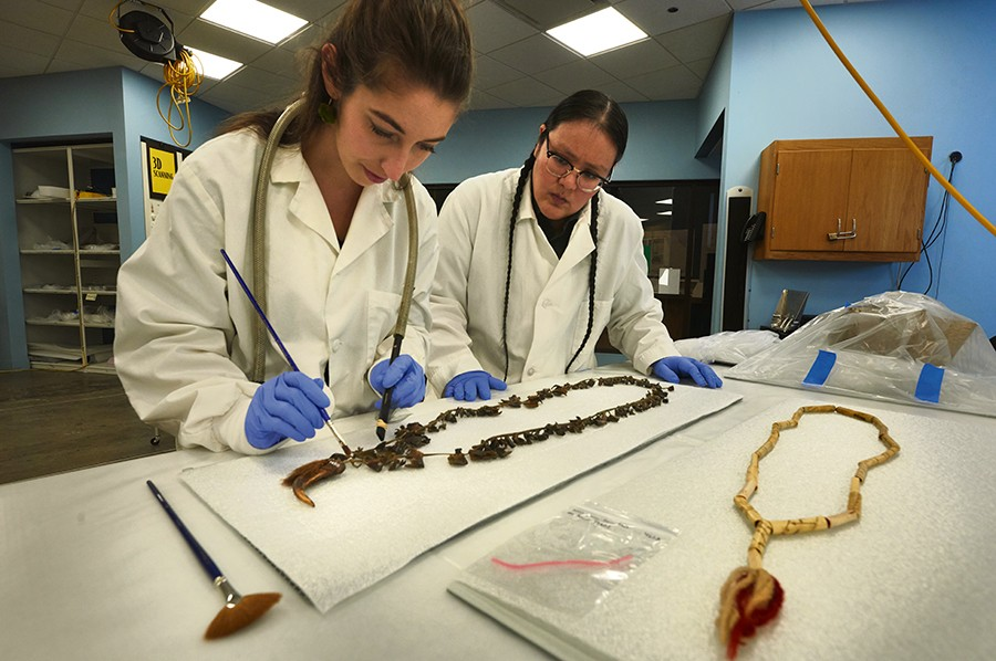 Field Museum conservation technicians Ellen Jordan (left) and J. Kae Good Bear work on an artifact in the Regenstein Lab. - JOHN WEINSTEIN