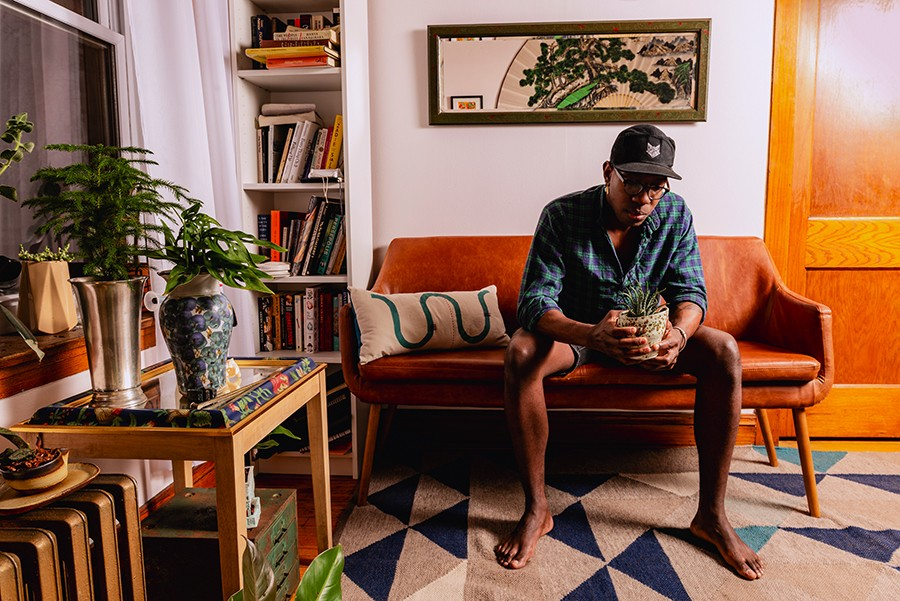 Damiane Nickles studies a small aloe plant in his living room. - RYAN EDMUND