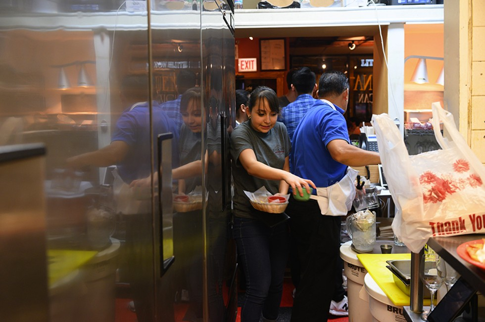 Yvette squeezes by her father, Benjamin. The kitchen's walkways are narrow, but they rarely slow down the family during the dinner rush. - GONZALO GUZMAN
