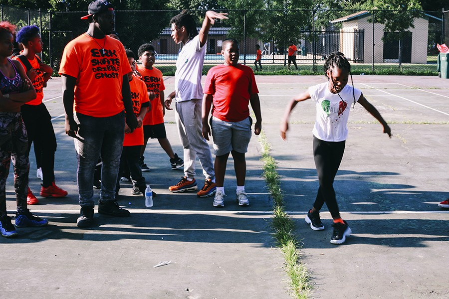 """Instructor Sterling """"Steelo"""" Lofton (third from right) and several campers look on while a student shows off her footwork moves. - LAWRENCE AGYEI"""