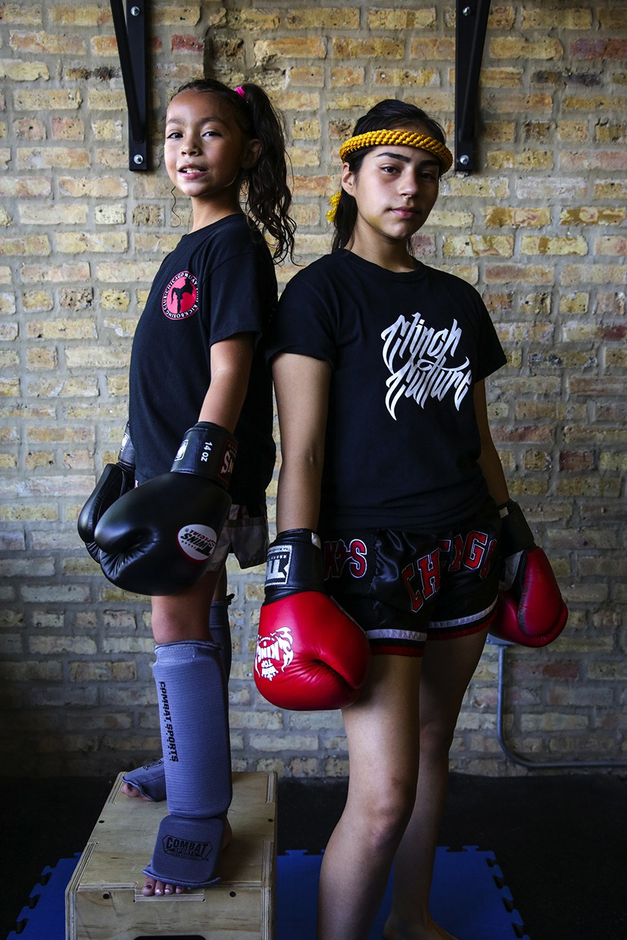 """Chanelle Ortiz, nine, and Paulina Lopez, 15, Portage Park Muay Thai  - Chanelle—""""I like Muay Thai because the punches and kicks are fun. I first started with boxing, but I was getting bored of boxing, so my dad took me here to learn some kicks. I think the kids at school should try Muay Thai because it's fun, and my coaches are really nice."""" - Paulina—""""It really means a lot to coach someone like Chanelle. She started at a younger age than me, and I'm sure she can go so much further. And she's so good now, too! It's fun to have someone who looks up to me and that does [Muay Thai] with me. It's like a team, me and her, our team against this guys' world."""" - GEOFF STELLFOX"""