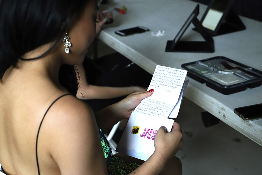Jade Lun reads a card before going onstage. Each participant receives an individual note of encouragement from Ng. - CAROLYN CHEN