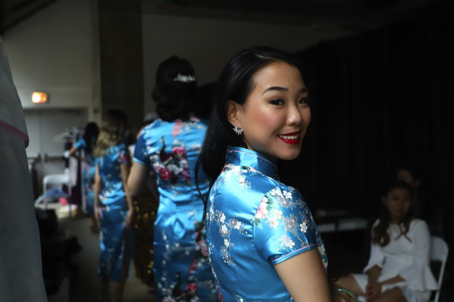 The contestants wait to go onstage in qipao, a traditional Chinese gown. - CAROLYN CHEN