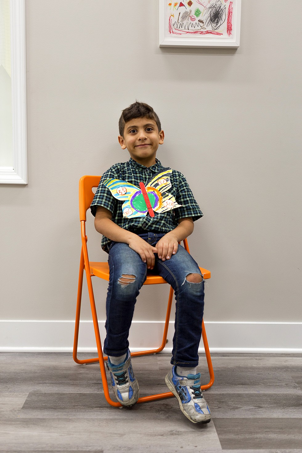 Sami, 7, presents a butterfly he made using mixed-media materials. Sami moved to Chicago from Syria with his family about three years ago. - FARAH SALEM FOR CHICAGO READER