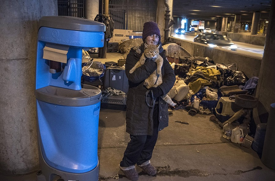 Stacey holds Simba and stands next to a portable wash station; March 15, 2020 - LLOYD DEGRANE