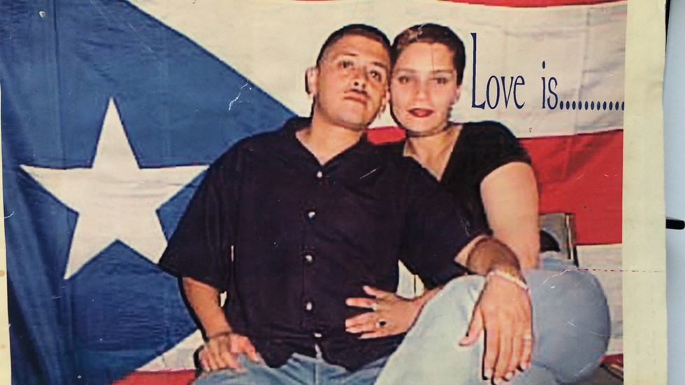 Justin Agrelo's parents, sitting happily in front of a bright Puerto Rican flag. - COURTESY JUSTIN AGRELO