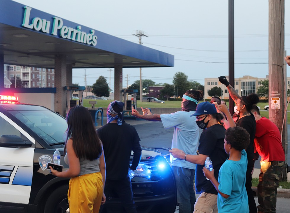 Roughly a dozen protestors work to push back an oncoming police car that was trailing their march on the evening of Tuesday, August 25, 2020. - ADAM MAHONEY / INJUSTICE WATCH