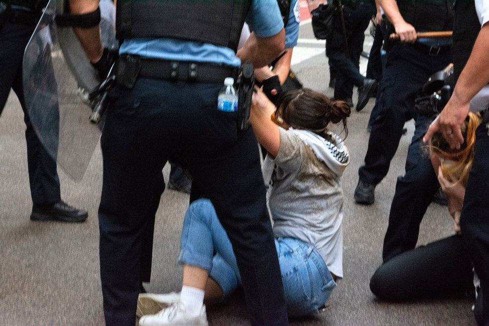 """Police arrest two activists who appear to have been hit with OC spray. In an arrest maneuver known as """"raking,"""" they dragged protesters along the pavement to handcuff them behind the skirmish line on Randolph Street. - DOMINIC GWINN"""