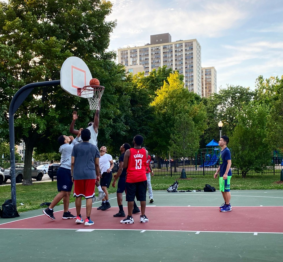 Ken Mason (red jersey) playing at the Clarendon Park basketball court in Uptown for the first time in July since the start of the pandemic. Mason had observed gentrified neighborhoods were less policed and impacted during the shutdown compared to the south and west sides of the city. - ALISON SALDANHA