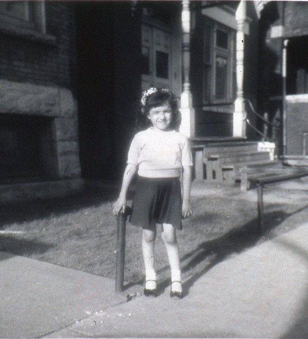 Cisneros as a child in front of the Chicago residence that informed  The House on Mango Street