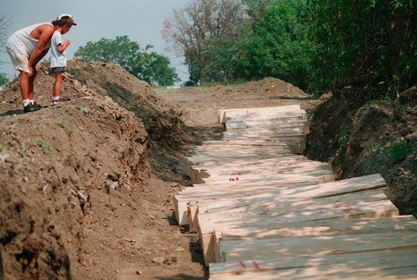 A man and his son visit a mass grave in Homewood, Illinois, where more than 40 forgotten and unclaimed victims of Chicago's 1995 heat wave were buried.
