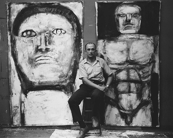 "Leon Golub photographed in the 1950s in front of two paintings from his ""Philosophers"" series"