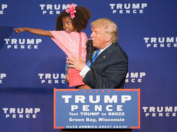 Trump hold the child of a supporter at an October rally in Green Bay, Wisconsin.