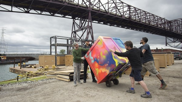 "Floating Museum members move a crate during the installation of ""River Assembly."""