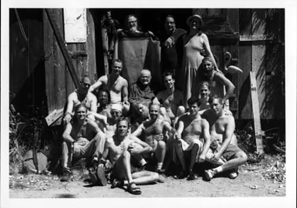 Harry Hay posing outside a shack with a group of men.