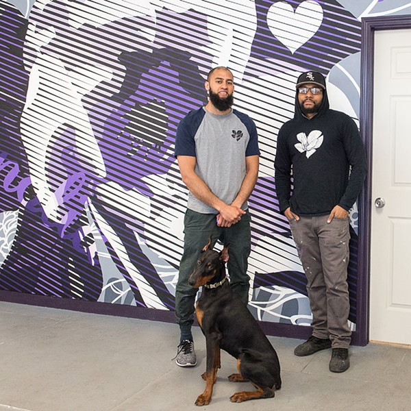 Omar Kamran, Justin Clemons, and shop dog Toph in front of Clemons's magnolia blossom mural.