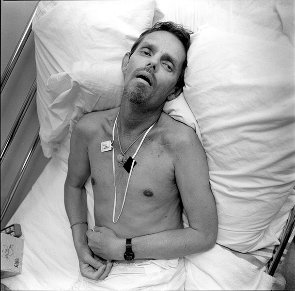 "Eight Months in the Death of Robert Thomas, 1991 from Faces of Aids: Life and Death at Bonaventure House, published March 27, 1992By Paul Meredith - Meredith says: ""When I first met Robert in August of 1990, he was still relatively healthy and strong. He was 41. He had eight months left. - Robert, who had made a good living selling real estate, was a detail person. He settled his financial affairs, arranged a living will, and purchased a vault for himself at Rosehill Cemetery. He labeled the drawers of his dresser so that when he became too weak to care for himself, the volunteers would know not to put his socks in his underwear drawer. As his condition worsened he seemed to relish smaller and smaller things: a poem read to him by a friend; the smell of the air in spring, his last. - For some residents, Bonaventure House is their only home, and its community their only family. Robert was one of these. His closest living relative, a sister somewhere in the south whom he loved very much, never came to visit him. She has two kids. She was afraid. He never complained. She sent a beautiful bouquet of flowers when he died."""