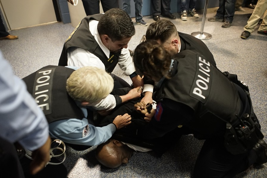 Four Chicago police officers take down a protester at the canceled Donald Trump rally Friday at UIC. - CHRIS RIHA
