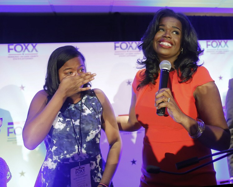 Kim Foxx, right, smiles at the crowd as her daughter, Kai, wipes tears from her eyes. - AP PHOTO/CHARLES REX ARBOGAST