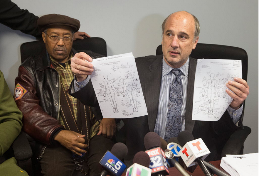 Ed Fox, right, lawyer for the family of Philip Coleman, displays autopsy records alongside Philip's father, Percy, during a 2015 press conference. - SCOTT OLSON/GETTY IMAGES