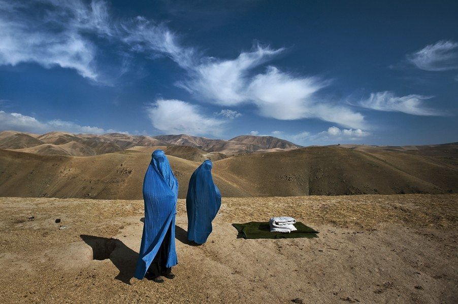 In Afghanistan, a stranded village woman and her pregnant daughter desperately try to find a ride to a clinic. - LYNSEY ADDARIO/NATIONAL GEOGRAPHIC