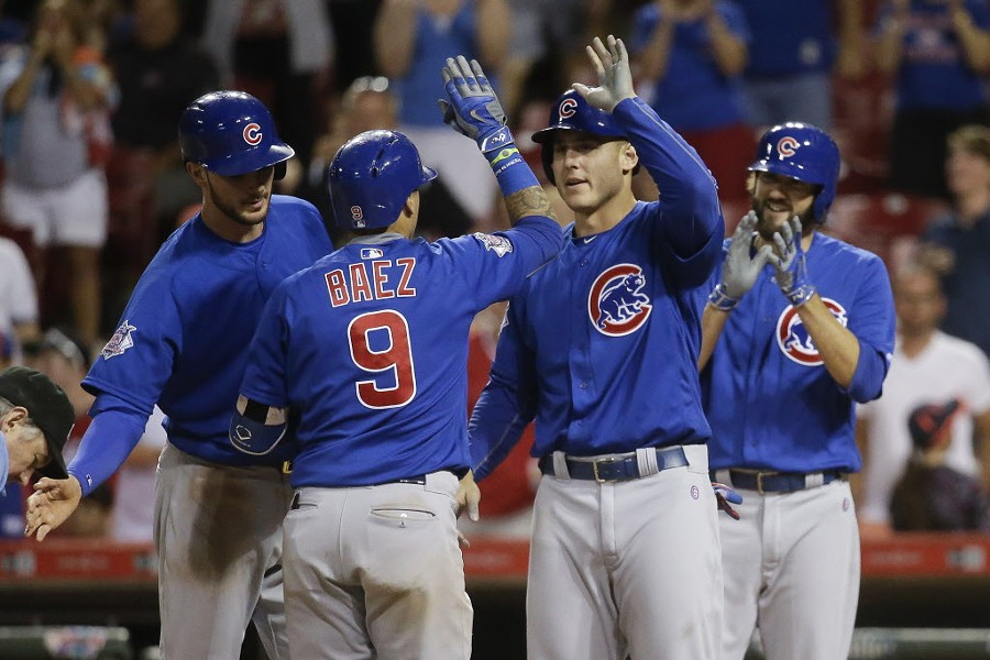 A 15th-inning grand slam by Javier Baez helped the Cubs win Tuesday night, as did three pitchers who played left. - AP PHOTO/JOHN MINCHILLO