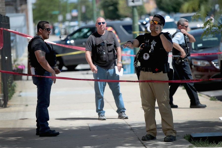 Police investigate a crime scene after two people were shot on the Near West Side on June 15. - SCOTT OLSON/GETTY IMAGES