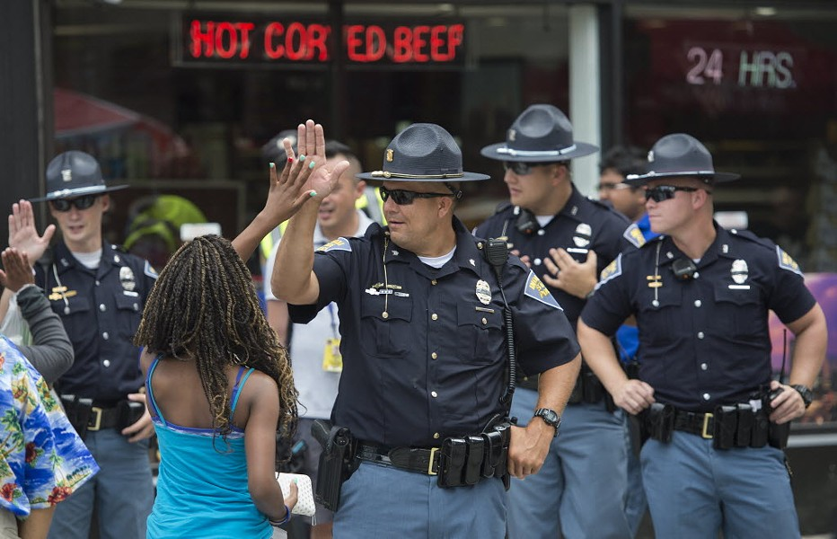 A woman high-fives a police officer outside the Republican National Convention in Cleveland on July 18. - ANDREW CABALLERO-REYNOLDS / AFP / GETTY IMAGES