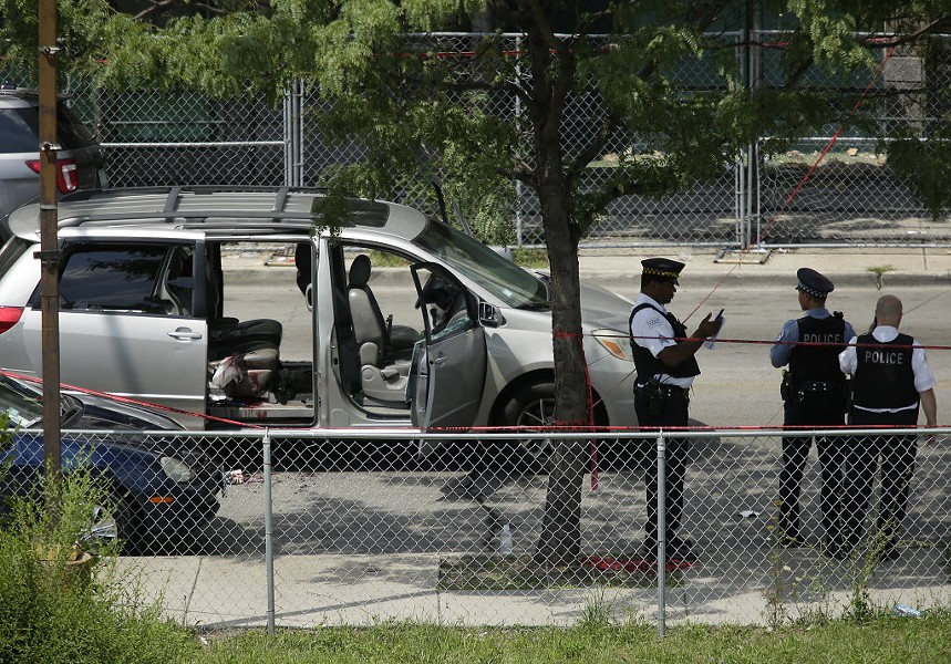 Chicago police officers investigate a July shooting. - PHOTO BY JOSHUA LOTT/GETTY IMAGES