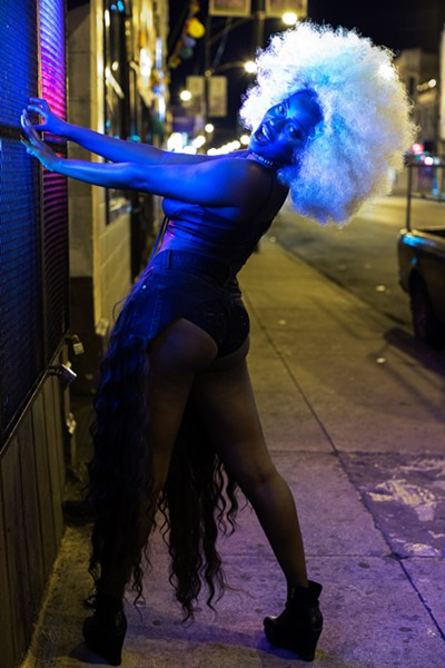 "Ebijimi uses her curly wigs to both critique stereotypes of black femininity and take pride in it. ""I am a black femme,"" she says. ""I only perform songs by black femmes. I reference a lot of black culture in how I dress."" - SUNSHINE TUCKER"