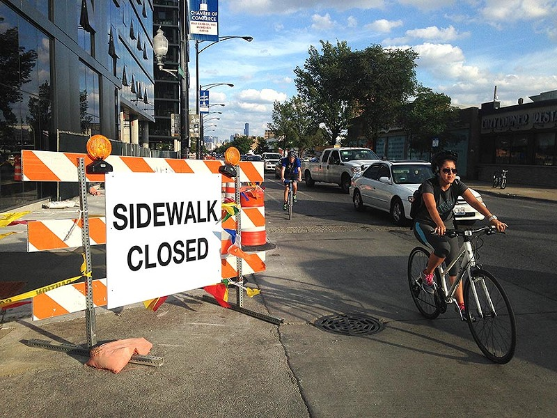 """Cyclists ride by Logan Square's """"Twin Towers"""" transit-oriented development. - JOHN GREENFIELD"""