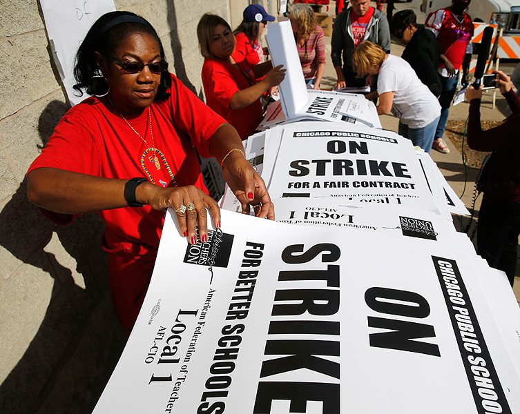Retired teacher Patricia Lofton counted a stack of picket signs Monday as the Chicago Teachers Union and Chicago Public Schools worked to avoid a strike. - AP/CHARLES REX ARBOGAST