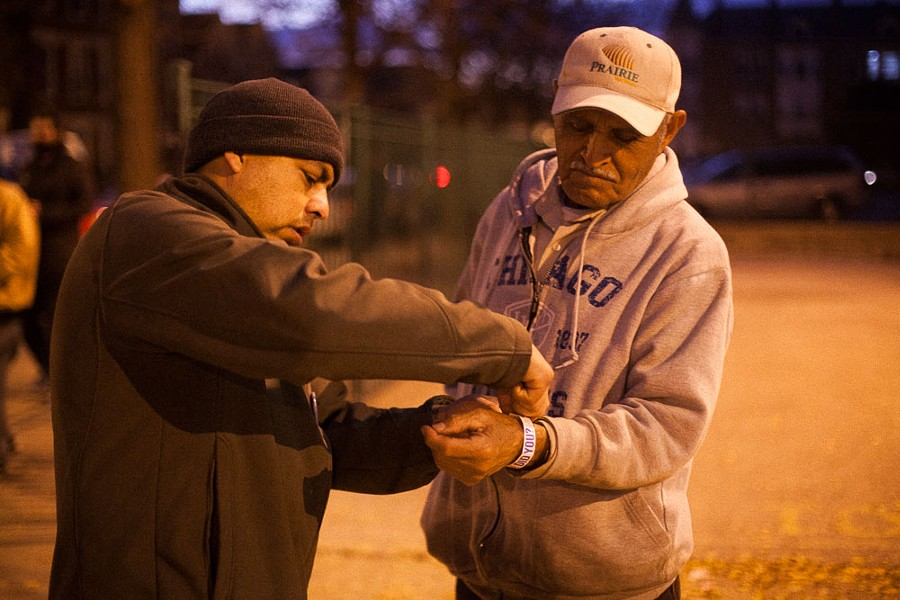 """Sergio Medina helps Lucio (no last name given) put on his """"I voted"""" bracelet outside Cooper in Pilsen. - DANIELLE A. SCRUGGS"""