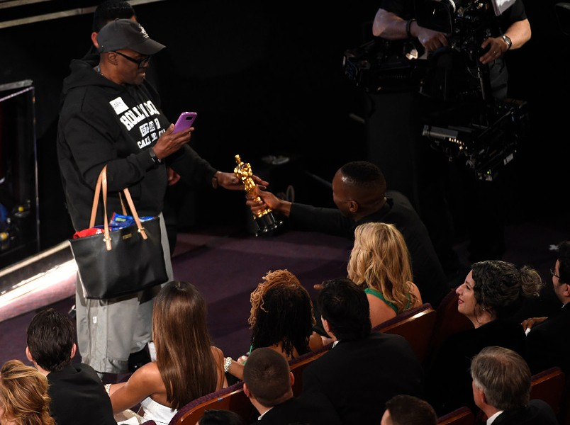 Mahershala Ali, right, hands his award for best supporting actor to a tourist named Gary during the Oscars Sunday night. - PHOTO BY CHRIS PIZZELLO/INVISION/AP