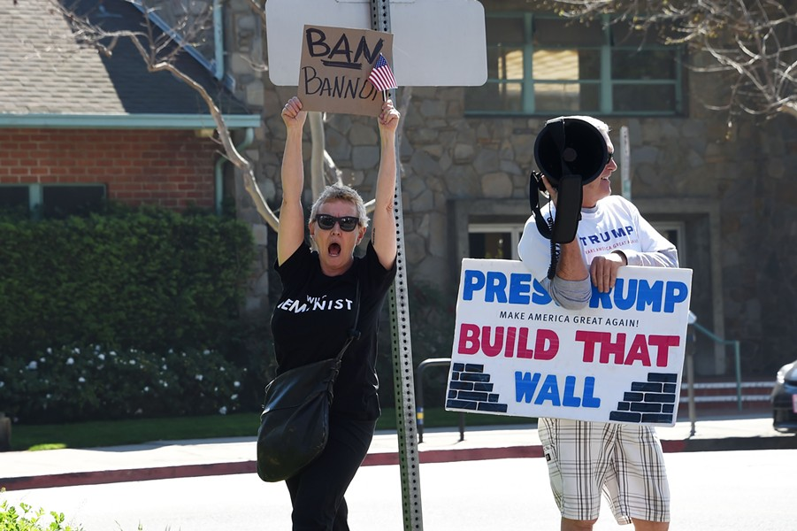 A protester, left, and a counterprotester hold signs at a demonstration against Breitbart News March 12 in Los Angeles. - AFP PHOTO / ROBYN BECK