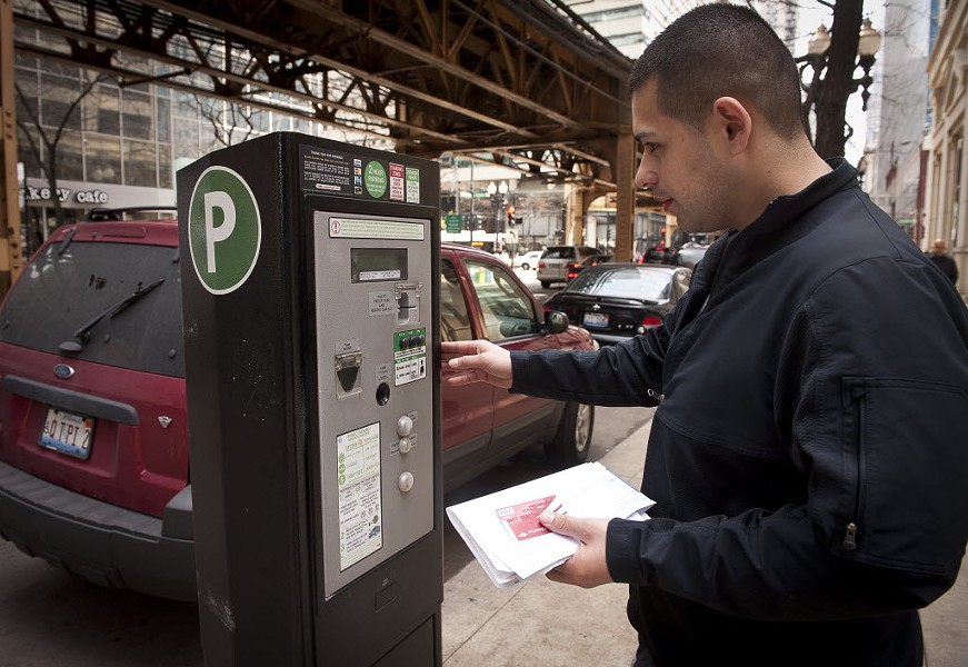Chicagoan Juan Gallardo uses a parking meter on Lake Street. - RICH HEIN/SUN-TIMES