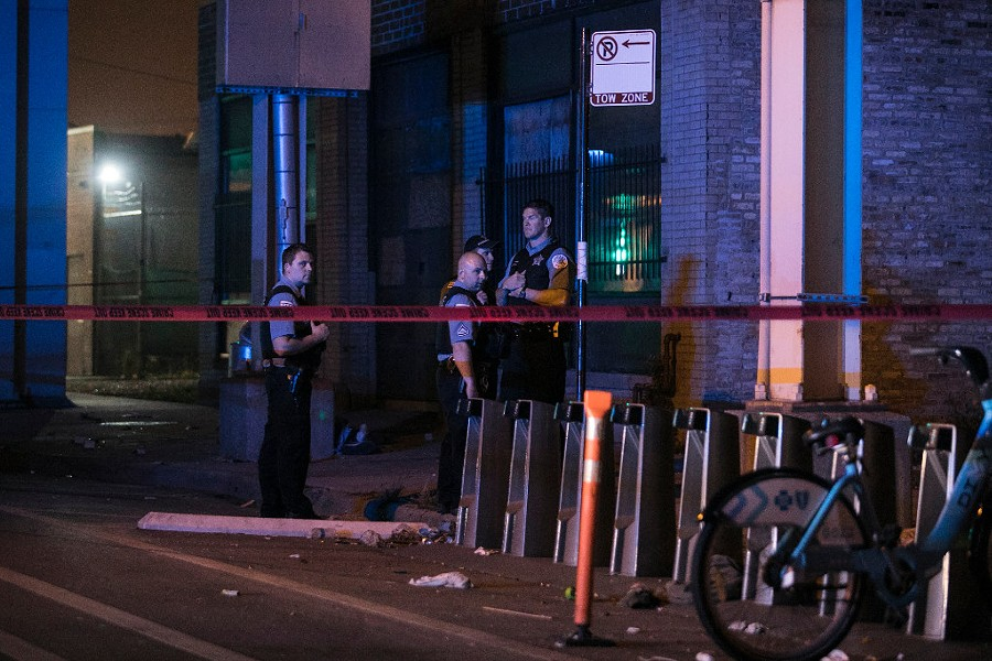 Chicago Police officers investigating the site of a fatal shooting in July - ASHLEE REZIN/SUN-TIMES
