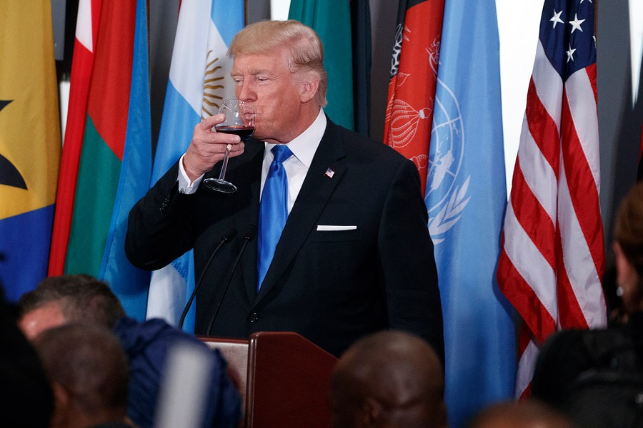President Donald Trump tips his glass after giving a toast during a luncheon at the United Nations Tuesday. - AP PHOTO/EVAN VUCCI